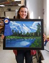 Student holding prize-winning landscape painting.