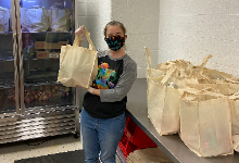 Kristy Garlitz holding a bag of groceries from the food pantry
