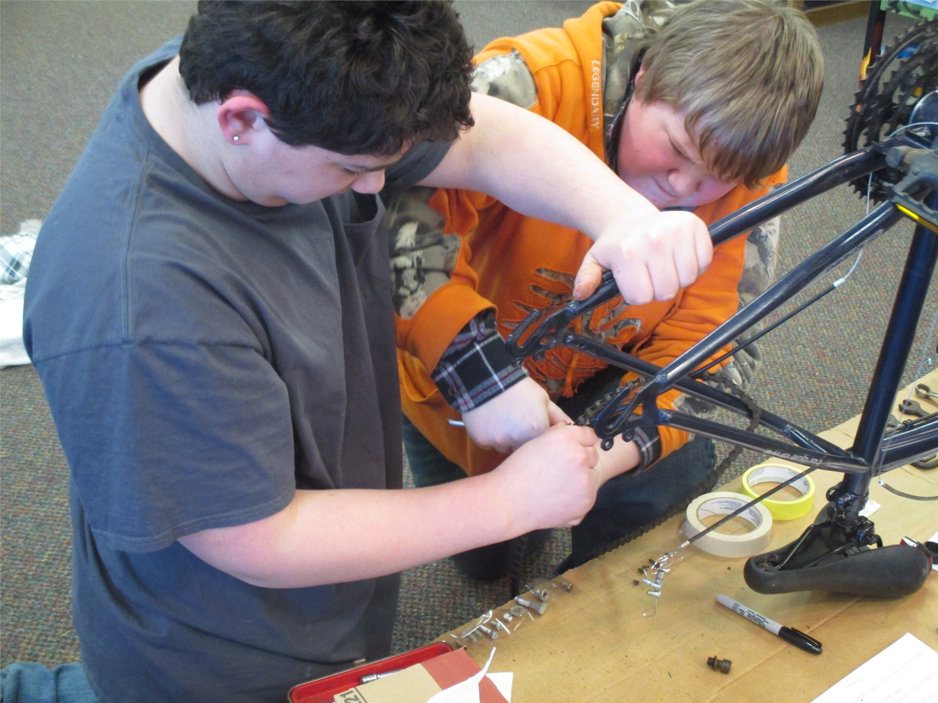 Image of study hall students in the library MakerSpace  disassembling a bicycle.