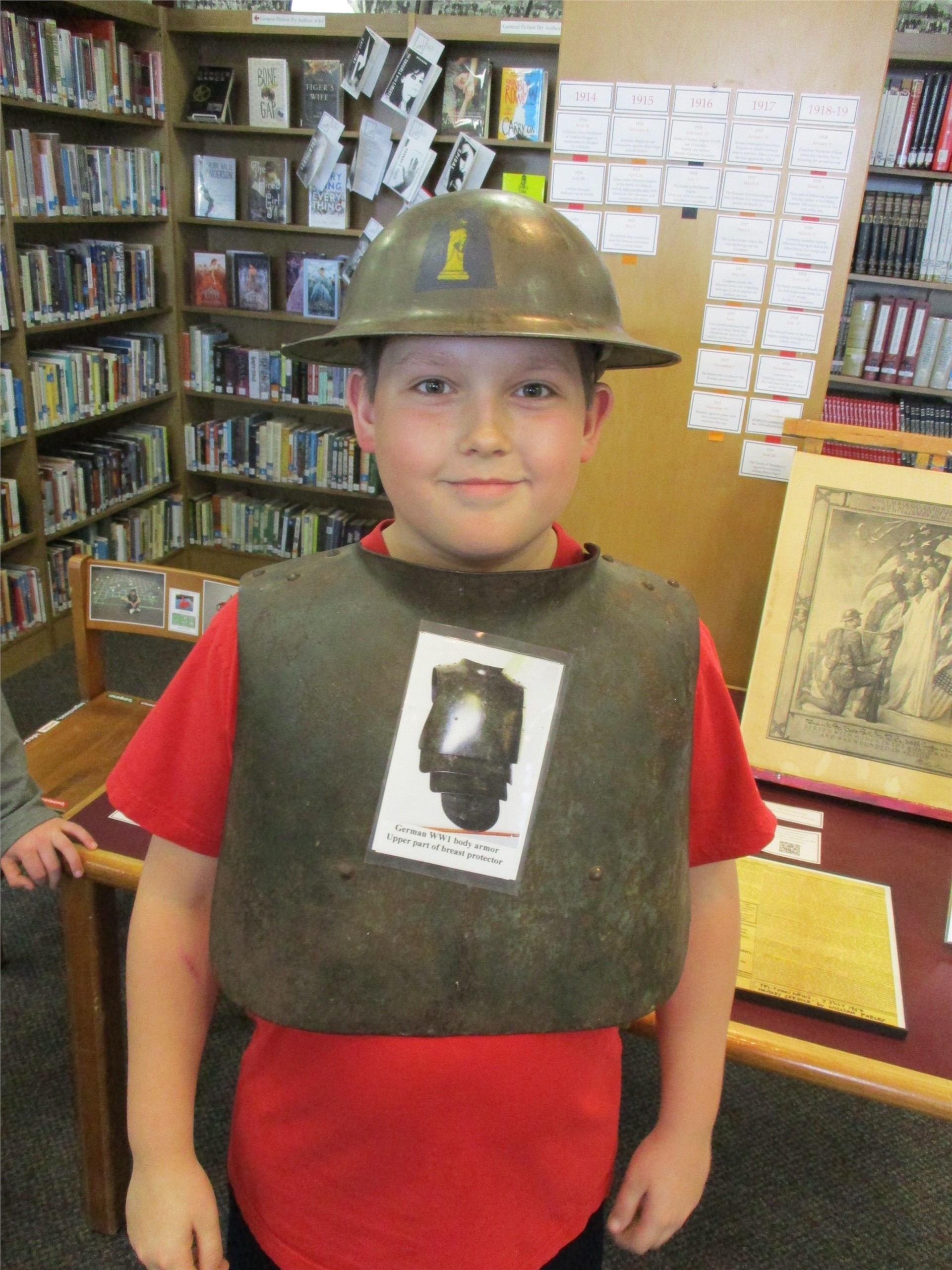 World War I exhibit: visitor wearing artillery armor and helmet.