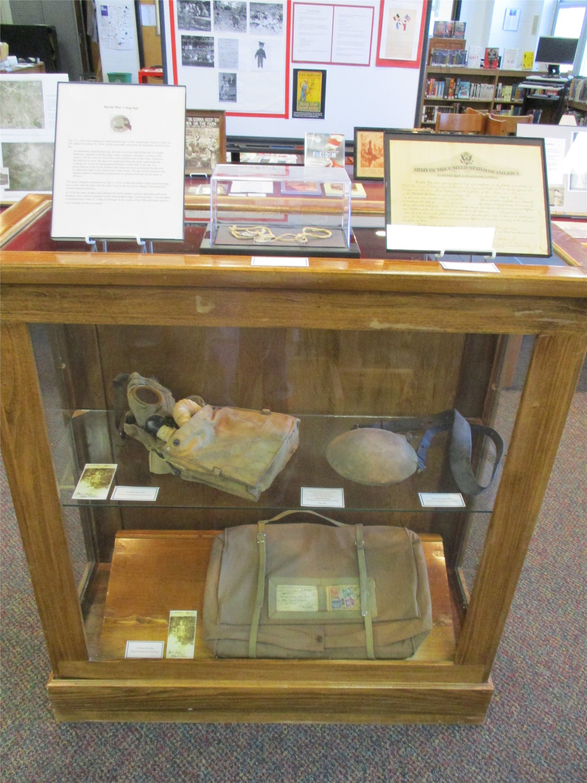World War I exhibit: display case featuring musette bag, canteen, and gas mask.