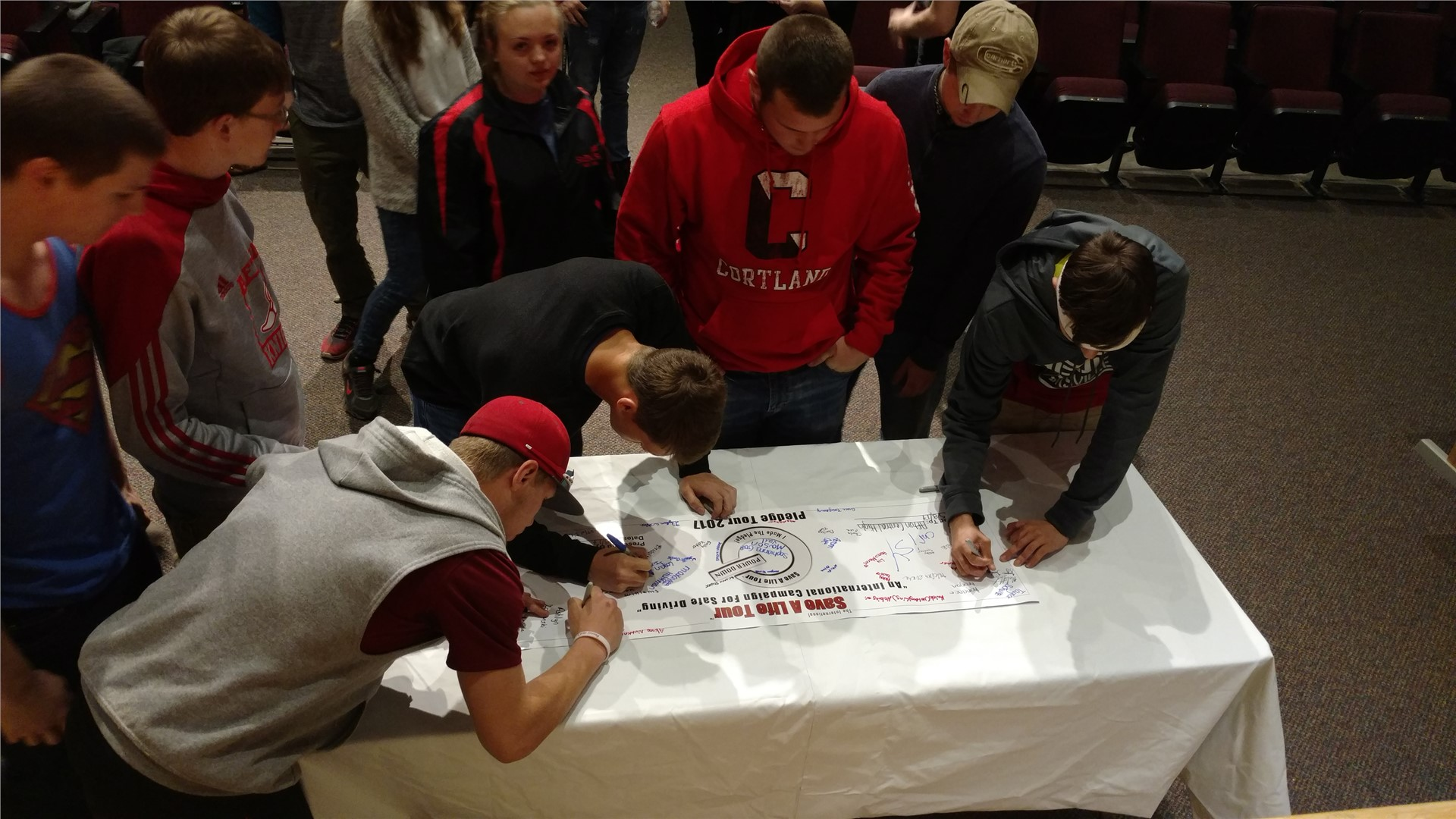 Students signing pledge banner.