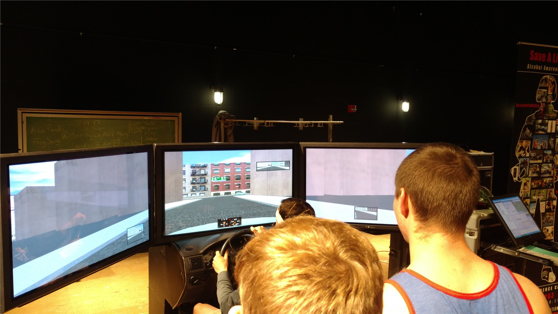 Student at console of virtual driving simulator as others look on.