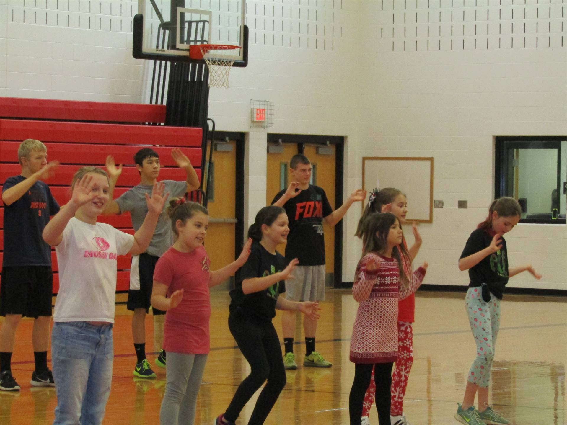 Students following dance instruction during gym class.