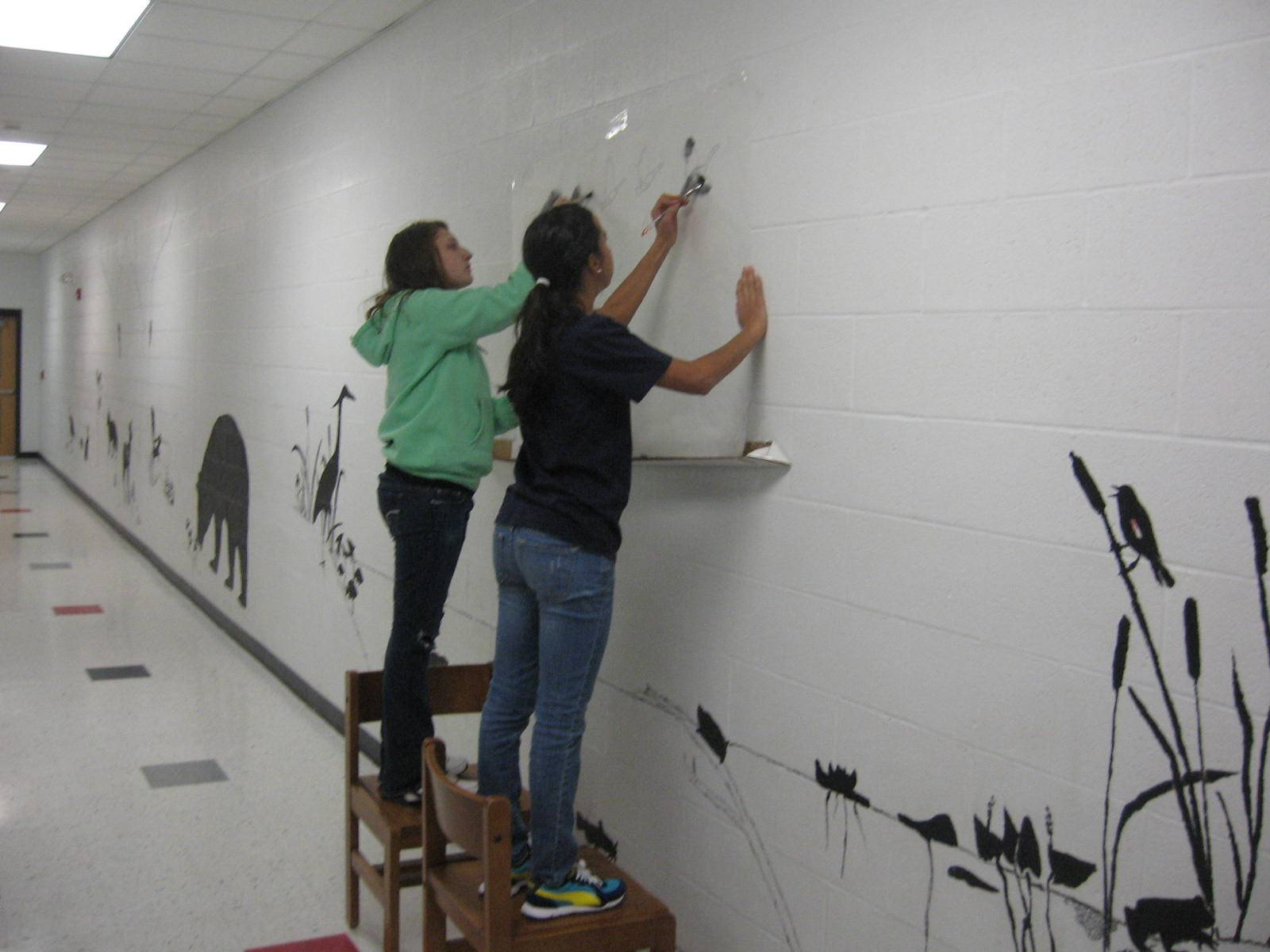 Students putting finishing images on Library wildlife mural.