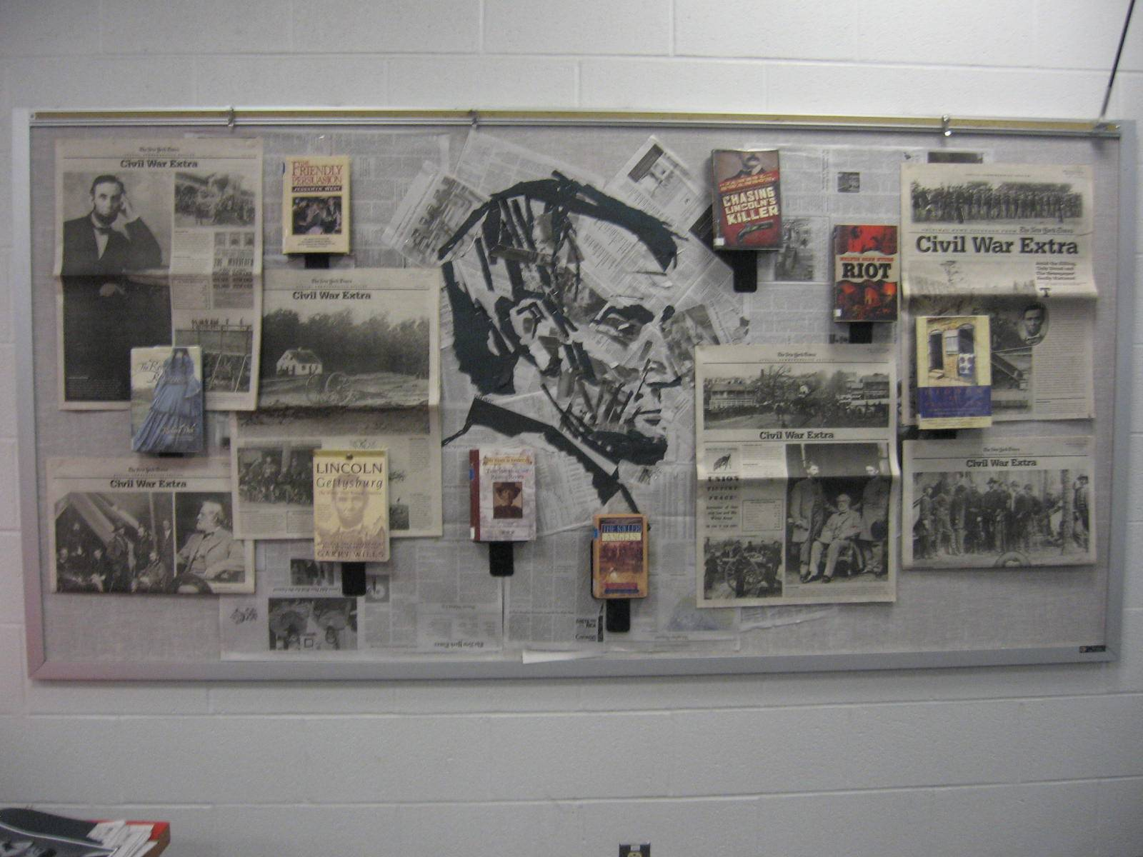 All things Lincoln: books, facsimile newspapers, cut-paper portrait.