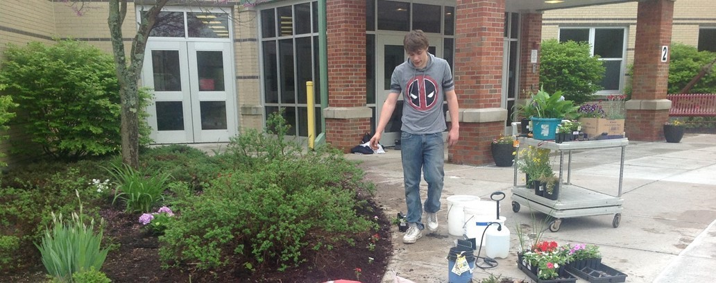 Senior students planting flowers at the entrance to the school.