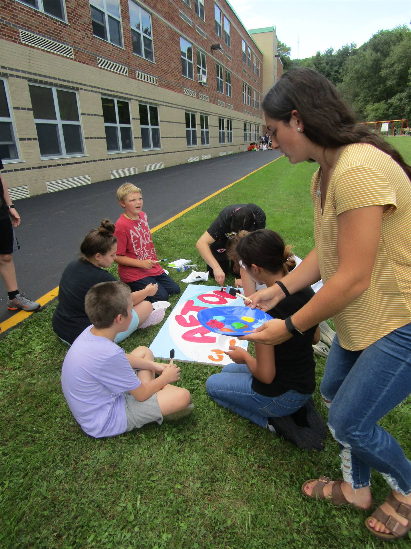 Elementary and MS/HS students work together to paint ceiling tiles for ACS.