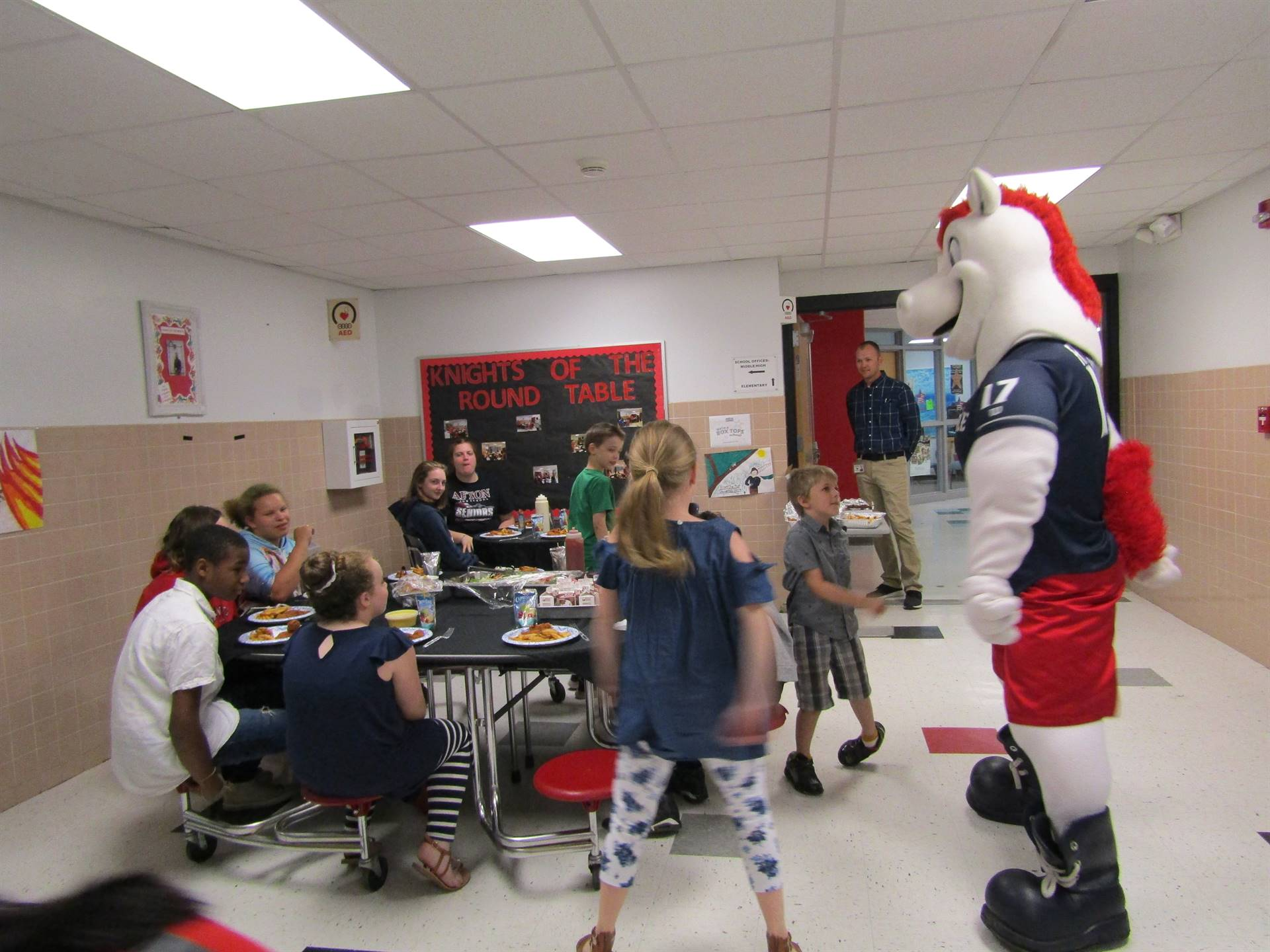 Students sitting around tables eating lunch with the Rumble Ponies mascot doing the floss