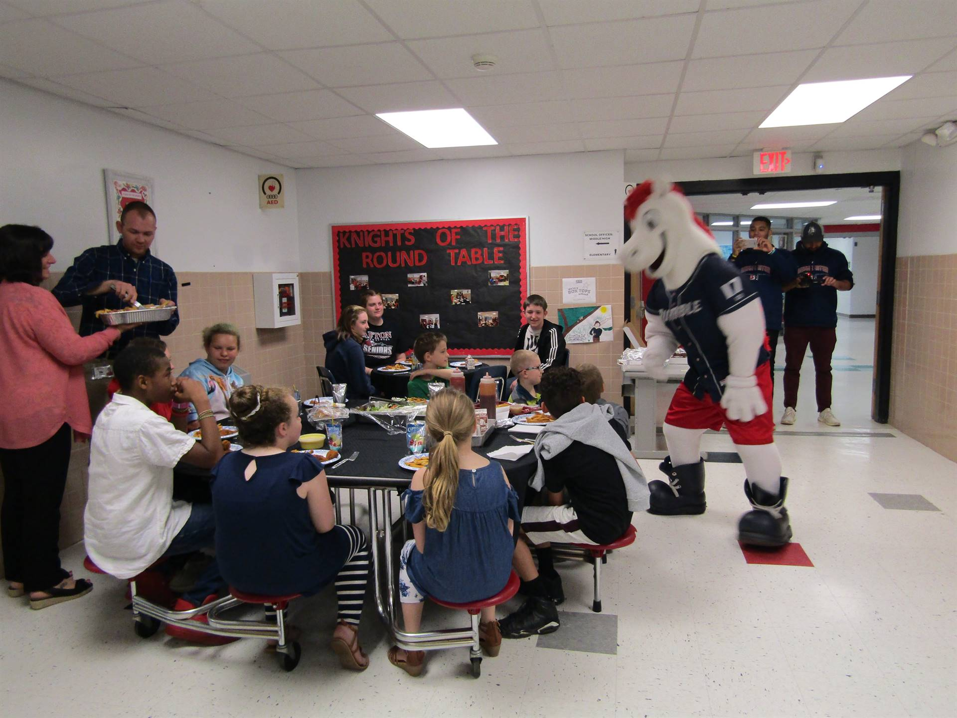 Students sitting around tables eating lunch with the Rumble Ponies mascot shaking hands