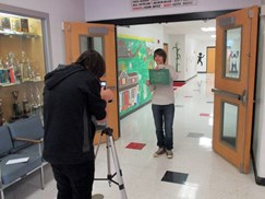 Image of two students filming a video in the hallway.