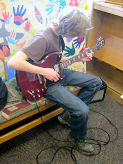 Image of a student playing a guitar using our library amp.
