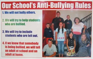 Poster containing children on staircase and listing the 4 anti-bullying rules