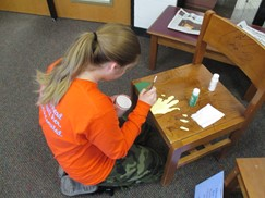 Image of student at work painting a library chair.