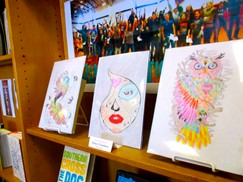 Image of three student drawings on a library shelf.