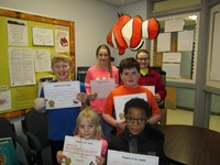 Multiple students holding certificates for student of the month