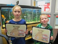 students holding bus certificates for the month of December